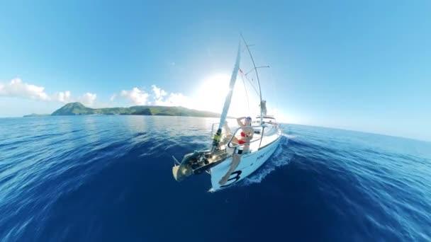 A vitorlás átkel a tengeren egy nővel, aki napozik a fedélzeten.