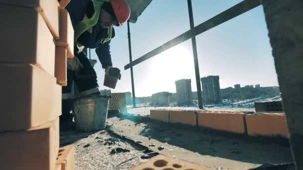 A férfi építész kőműves egy folyamatban lévő épületben.