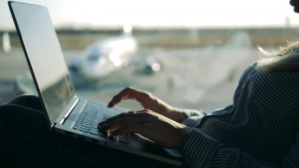A laptopot egy nő üzemelteti a reptér ablaka mellett.