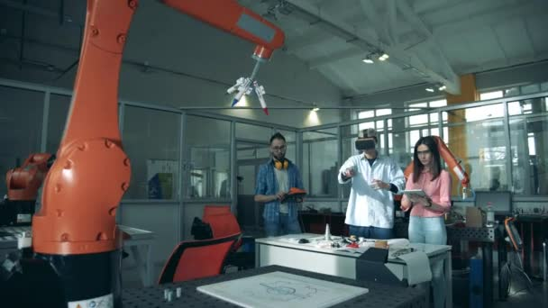Virtual experiment with a robotic arm is being held by the researchers Young engineers working in innovative laboratory.