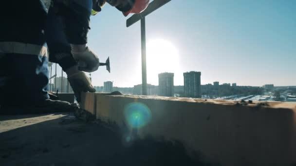 Dělník používá lopatku při kladení cihel.