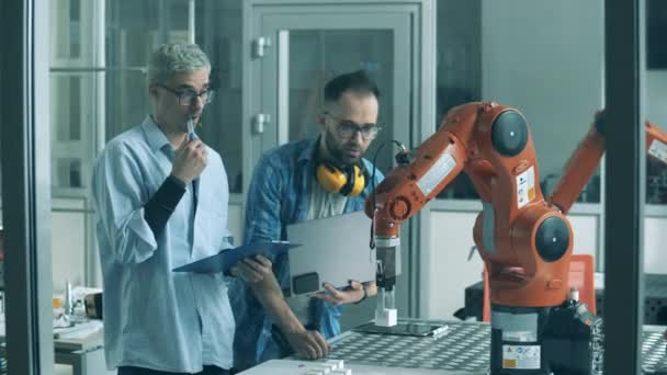Male engineers are analyzing a robotic arm in motion