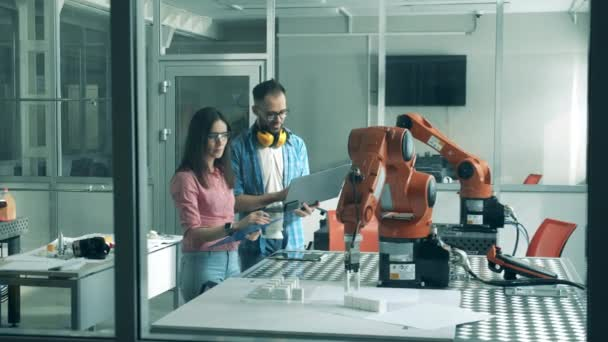 Robotic arm in motion is being observed by two engineers
