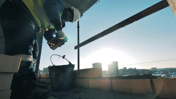 Építési munkás egy építkezésen. A téglaépítést egy férfi építész végzi.