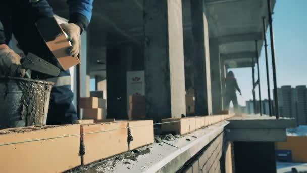 A munkások kőművesmunkát végeznek egy projekt területén. Építési munkás egy építkezésen.