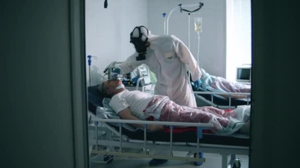 Egy orvos ellenőrzi a betegek hőmérsékletét a kórteremben a coronavirus pandémia alatt..