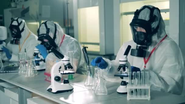 A védőruhás munkások mikroszkóp alatt vizsgálják a szondákat..