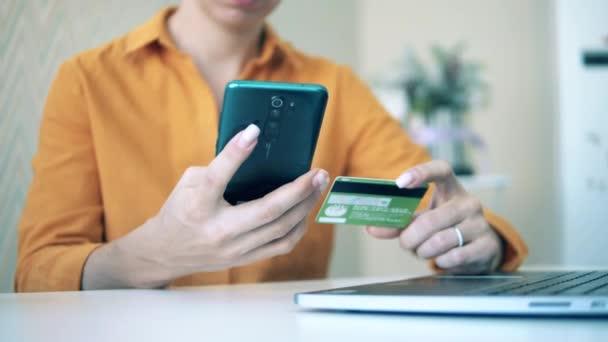 Egy nő kártyával és okostelefonnal vásárol online