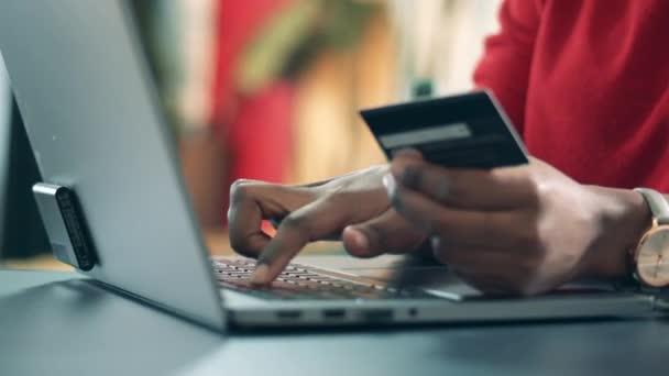 Großaufnahme weiblicher Hände, die Kartendaten in einen Laptop eingeben