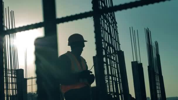 Stavitel opravuje armaturu při práci na staveništi.