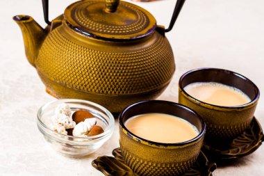 """Картина, постер, плакат, фотообои """"Индийский пряный чай с молоком. Чайник, две чашки и сладости"""", артикул 181001132"""