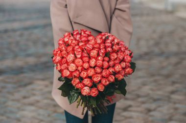 the girl has received a gift a huge bouquet of coral bright roses