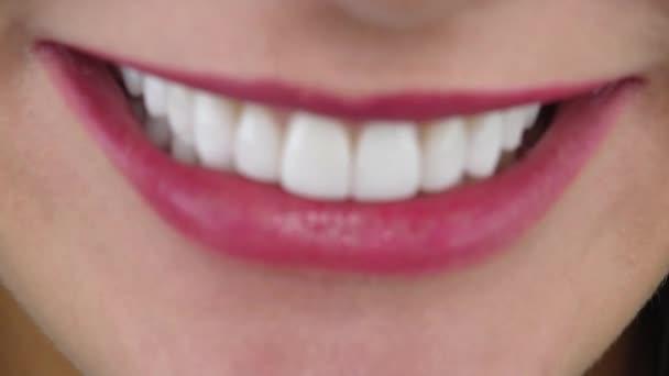 Frau mit erstaunlichem Lächeln durch Veneers beißt rosa Lippenmakro