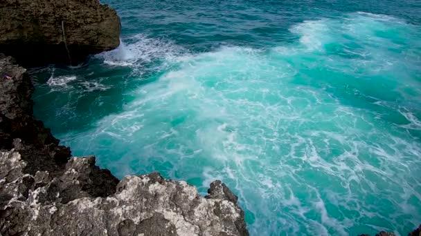 Az Indiai-óceán hullámai lezuhannak a sziklás parton. A fehér hab lassított felvételen fut a sziklás parton. Tiszta kék türkiz tenger víz fröccsenő kövek körül