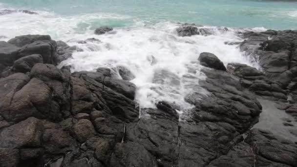 Az Indiai-óceán hullámai lezuhannak a sziklás parton. A fehér hab lassítva fut a sziklás parton.