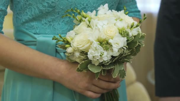 Bride holding a wedding bouquet in a wedding hall