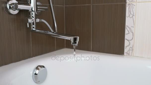 Vodní proud teče z kohoutku voda do vany