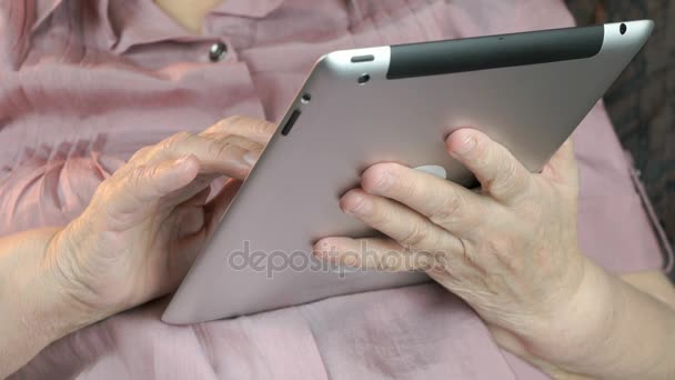 Stará žena držící stříbrný tabletový počítač