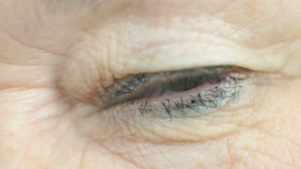 60-jährige Frau öffnet und schließt ein Auge