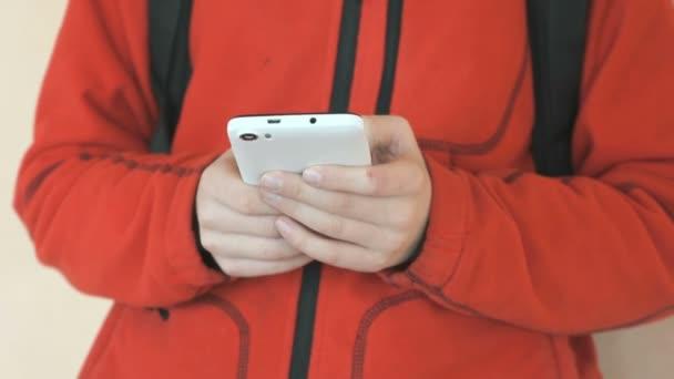 A tinédzser bent tartja a fehér mobiltelefon