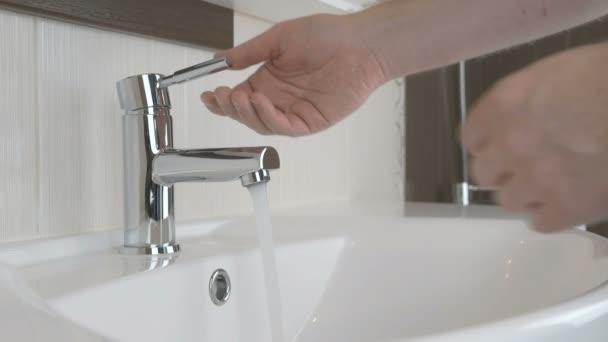 Muž mytí rukou v koupelně