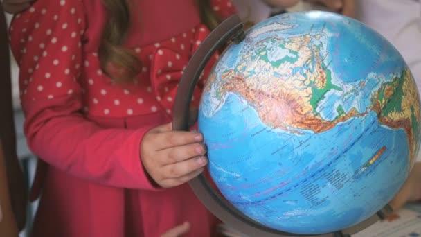 Předškolní dívka otáčí model světa světa