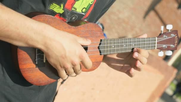 Young guy playing an acoustic guitar outdoors