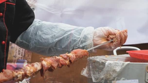Mužské ruky zavěšování kousky syrového masa na špízu