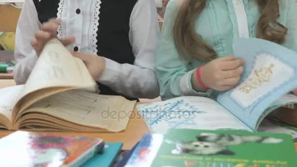 Předškoláky sedí u stolu otočí stránky knihy