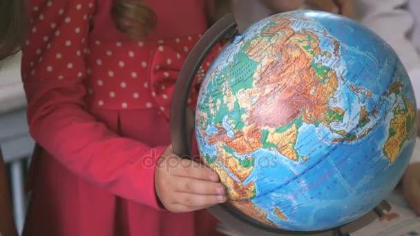 Malá holka otočí zeměkoule světa. Detail