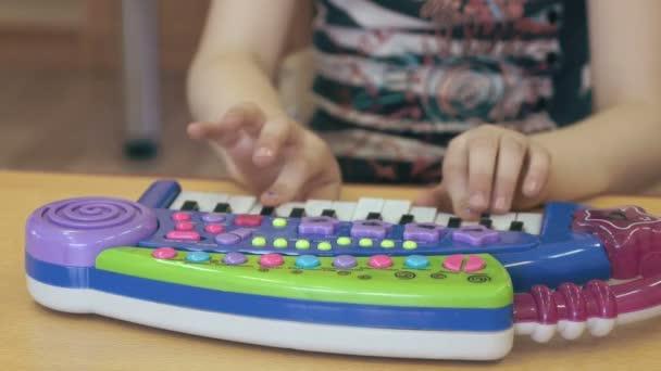 Dítě holčička hraje na klavír hračky