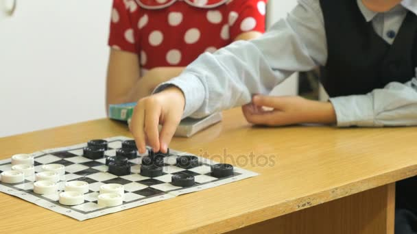 Little kids play checkers at kindergarten.Close-up