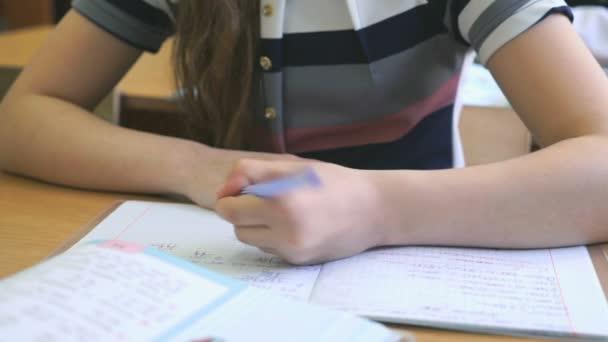 Školačka píše v poznámkovém bloku s kuličkovým perem