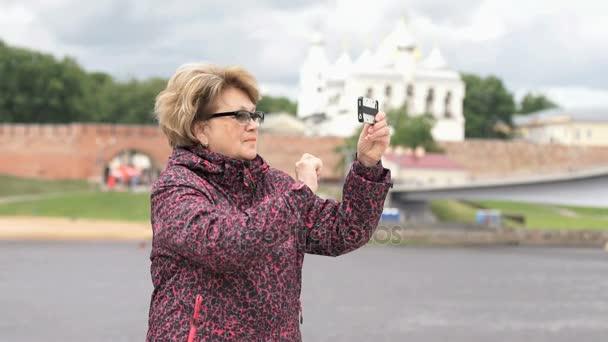 Dospělé ženy brát fotografie pomocí stříbrné chytrý telefon
