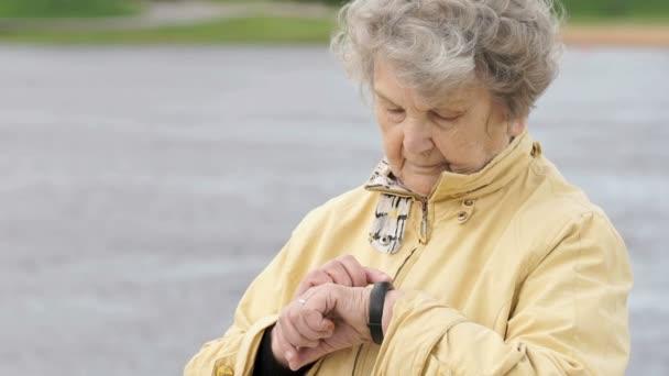 alte Frau schaut auf Fitness-Tracker am Armband
