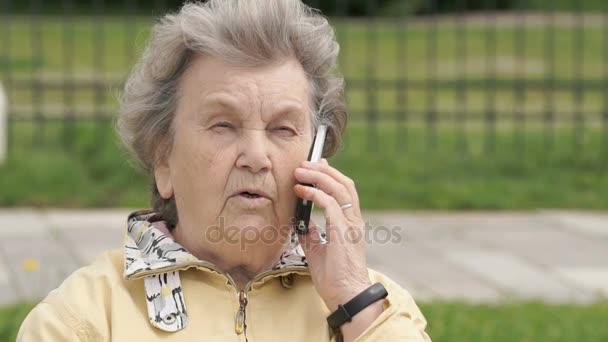Zralá žena mluví o mobilní telefon venku