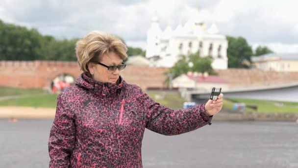 Dospělé ženy ve věku 60 let brát fotografie pomocí smartphonu