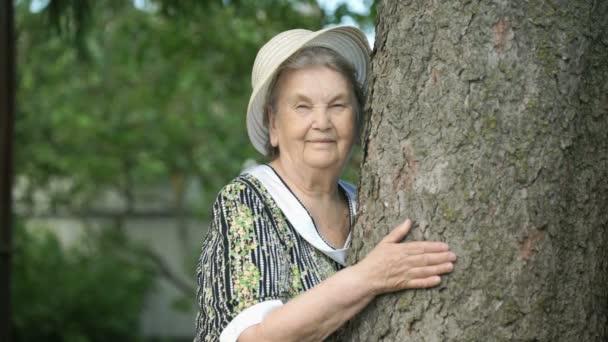 Ältere Frau, die Baum umarmt, lächelt in die Kamera