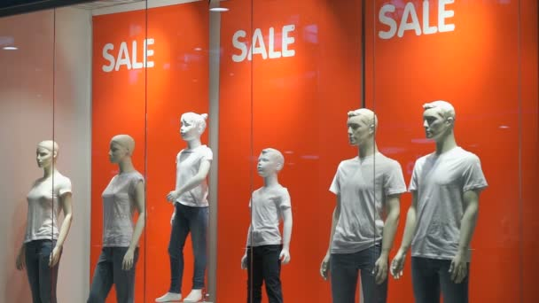 A shop window with mannequins indoors  Words SALE