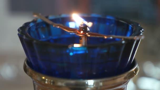 Lampada a olio chiesa con una candela accesa nel tempio u video
