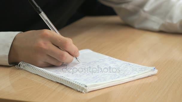 Diák írja szöveget a füzet, toll
