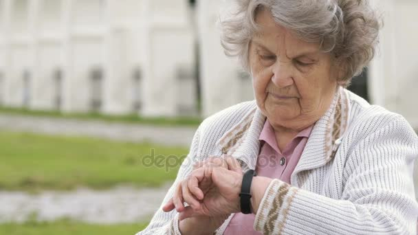 Old woman looking on wristband fitness tracker
