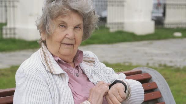 Elderly woman looking on wristband fitness tracker