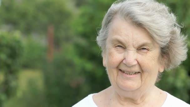 Porträt einer lächelnden älteren Frau im Freien