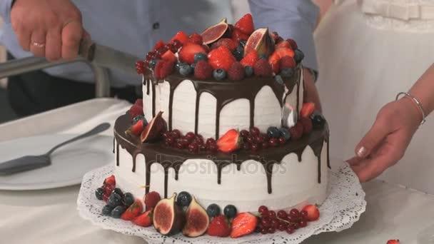 Novomanželé řezání lahodný sladký svatební dort