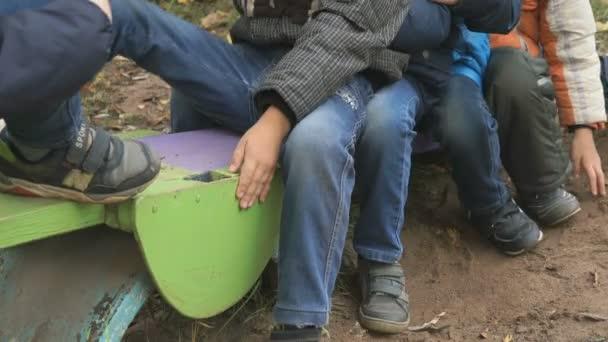 Skupina děti na houpačce sedí pohromadě