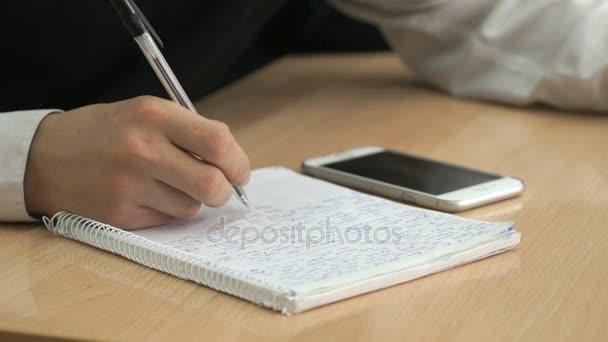 Diák szövegét írásban jegyzetfüzet toll használatával