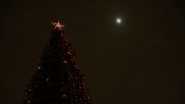 Vánoční strom mrkající proti měsíci