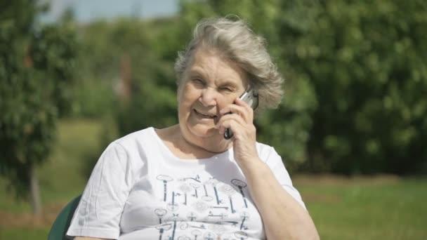 Usměvavý postarší žena mluví, pomocí chytrého telefonu