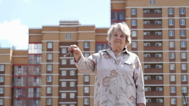 Lächelnde ältere Frau hob die Hand mit Schlüssel